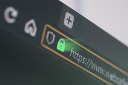 Dark web browser close-up on LCD screen with shallow focus, light shining through https padlock. Internet security, SSL certificate, cybersecurity, search engine and web browser concepts