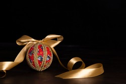 Dark wood Christmas copy space: decoupage christmas isolated ball close up with gold satin ribbon in black background