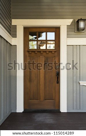Dark wood front door of a home. View of a rustic front door on a light gray home during the day. Vertical shot.