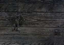 Dark wooden boards, planks. Naturally aged wood, natural brushing process. The top view. Close-up. The stock photos.