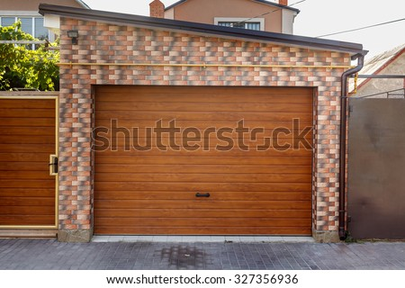 Dark Wooden Garage Door with colored brick wall background