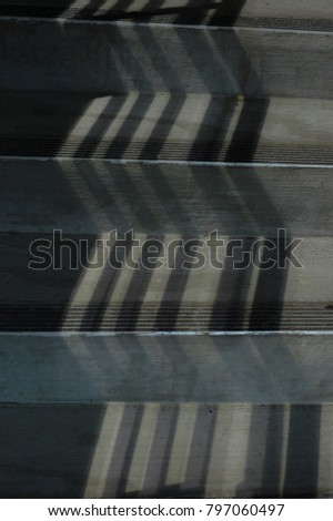 Dark zigzag shadows down a gray stairway at night, abstract texture background.  #797060497
