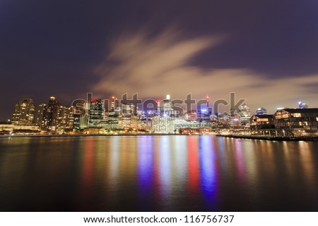 Darling Harbour panoramic view of Sydney CBD skyscrapers in Australia at sunset with reflections of lights in bay water from Pyrmont