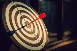Dart arrow hit on bulleyes of dartboard to represent that the business reached the target  with dark tone picture style. Target and goal as concept.