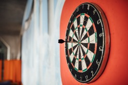 Dart arrow hitting in bulls eye on dartboard.Success hitting target aim goal achievement concept.Indoor game,played at home.Throwing small missile into dartboard.
