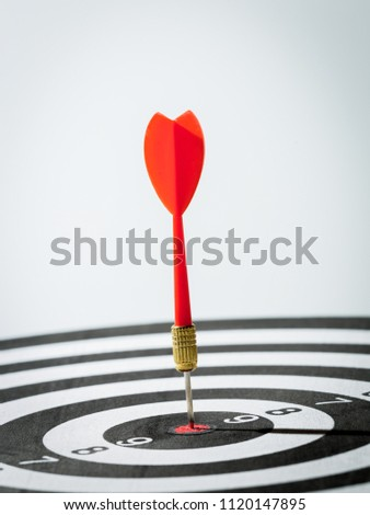 dart arrow hitting in the target center of dartboard. concept of the success