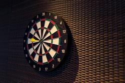 Dart arrow hitting in the target center of dartboard. Darts board.Success hitting target aim goal achievement concept background
