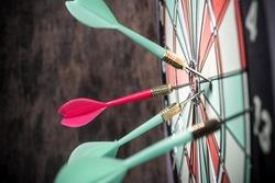 Dart in bulls eye of dartboard concept for hitting target dart success concept