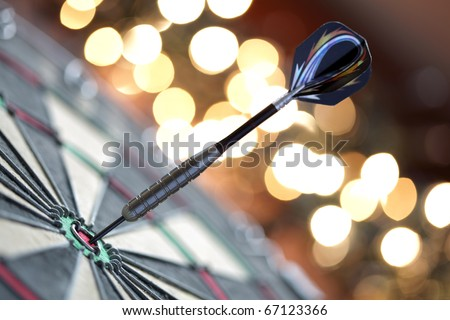 Dart in bulls eye of dartboard with shallow depth of field concept for hitting target