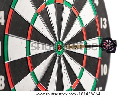 Dart in the center of a dart board scoring a bulls eye conceptual of winning, accuracy, skill, challenge and achievement, isolated on white