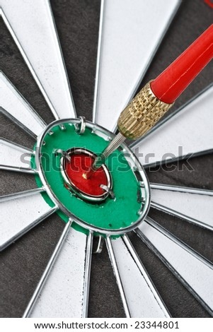 Dart on bull\'s eye of a dartboard. Close up.