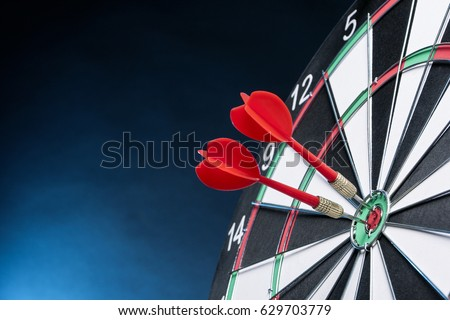 Dartboard on a blue background with arrows hitting the center target Stockfoto ©