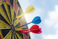 Dartboard on a blue background with arrows hitting the center target. Business target or goal success and winner concept. Aim, darts , dartboard, marketing, target