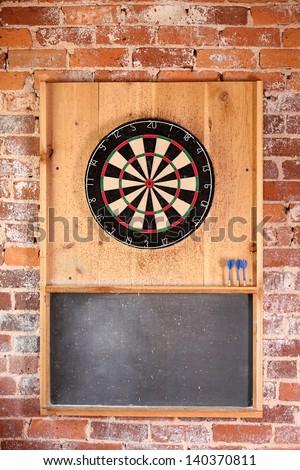 Dartboard on brick wall with chalk board score board and darts.