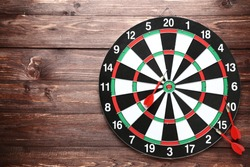 Dartboard with darts on brown wooden table