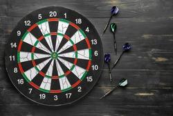 Dartboard with darts on dark wooden background