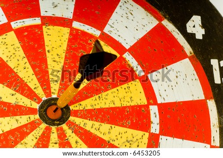 Dartboard with single dart in the middle or bulls -eye.  symbol of hitting the target or making the goal