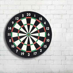Darts board on a white brick wall with copy space. Classic dartboard with twenty black and white sectors