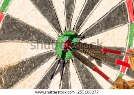 Darts board with three arrows in bullseye