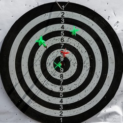 Darts hit the target. Darts is a game in which players throw darts at a round target.