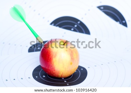 Darts in apple.Concept of success. - stock photo