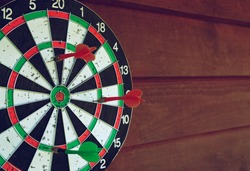 Darts over wooden background. Arrows missed target. Coyspace for text.
