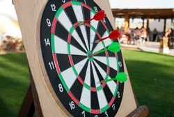 Darts with arrows. Playing darts during summer day. Arrows reached the target. Game over.