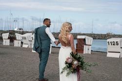 Das deutsche Brautpaar geht auf dem Strand des Ostsees, sie hält ihre Hände fest. Die Braut hat eine große Brautstrauß in der Hand und freien Rücken.Die Beiden sind von Hinten und von Weiten zu sehen.