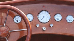 Dashboard and steering wheel of a classic wooden speed boat showing all the controls.