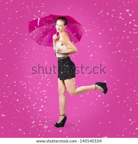 Dashing retro pinup girl popping up one leg with umbrealla when doing a rain dance in fifties fashion. Pink background