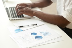 Data analysis and business statistics concept, african-american businessman using laptop analyzing work result infographic stats graphs and charts, making report or strategic planning, close up view