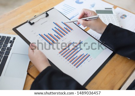 Data analysis, Financial accountants are evaluating company revenue data using calculators and databases to compute and summarize for leaders, Young women working.