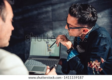 Data analyst pointing at report on the laptop to his coworker in the office