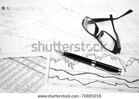 data analyzing in stock market: on the charts and quotes prints, the eyeglasses and a pen - stock photo