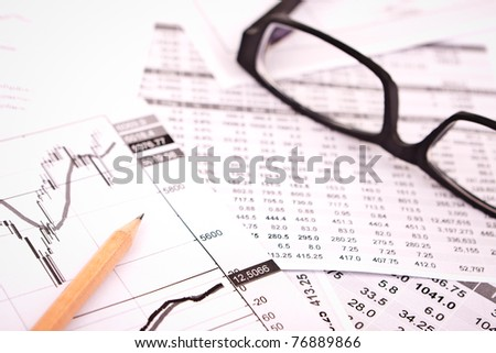 data analyzing in stock market: on the charts and quotes prints, the eyeglasses and a pencil