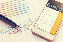 Data analyzing with calculator mobile phone and pen. from charts and graph to find out the result.