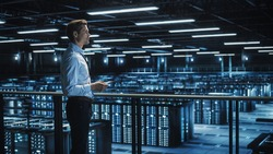 Data Center Engineer Using Digital Tablet Computer, Maintenance Specialist. High-Tech Information Protection, Cyber Security. Cloud Computing Facility. Server Farm for Iaas, saas, paas.