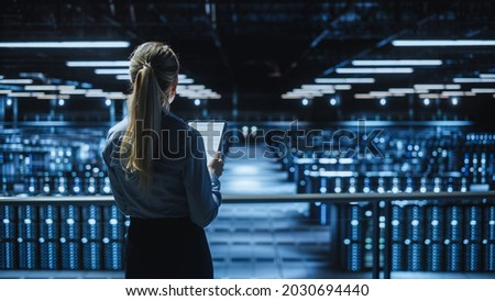 Data Center Female Programmer and Maintenance IT Specialist Overlooking Cloud Computing Server Farm. System Administrator Working on Cyber Security for Iaas, saas, paas. Back View Shot