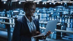 Data Center Female Programmer Using Laptop Computer, Maintenance IT Specialist. In Cloud Computing Server Farm Smiling System Administrator Working on Cyber Security for Iaas, saas, paas.