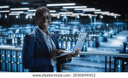 Data Center: Female Programmer Using Laptop Computer, Smiling and Looking at Camera. In Cloud Computing Server Farm System Administrator Working on IT Maintenance for Iaas, saas, paas.