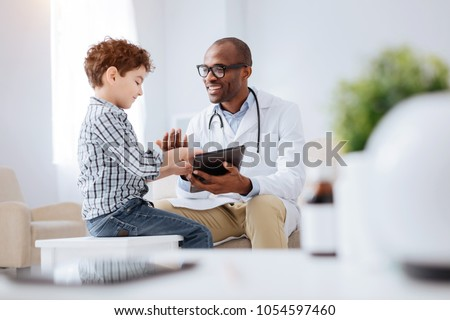 Data in tablet. Energetic cheerful male doctor grinning while showing tablet to boy and sitting