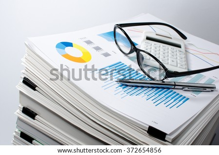 Data management. Document management. Business concept. Pile of documents on gray background. Graph, glasses, calculate and pen.
