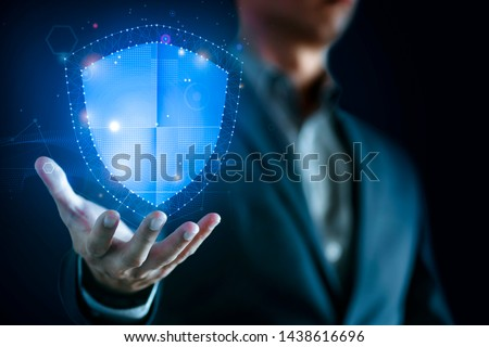 Data protection and network security concept. Glowing light Shield on business man hand for internet fire wall protect, insurance, or computer virus cleaner.