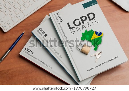Data protection laws concept: three books on a wooden table with names of three data protection laws on their cover: ccpa, gdpr, lgpd