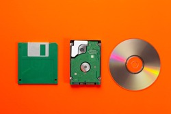 Data storage medium evolution - floppy disk, CD Disk, small hard disk drive on orange background. Top view