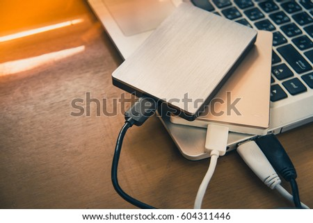 Data transfer from laptop computer to external hard disk for backup files and important information using USB 3.0 connection, wooden table background.