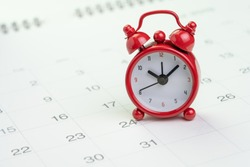 Date and time reminder or deadline concept, small red alarm clock on white clean calendar with number of day, counting down to holiday, vacation or end of month.