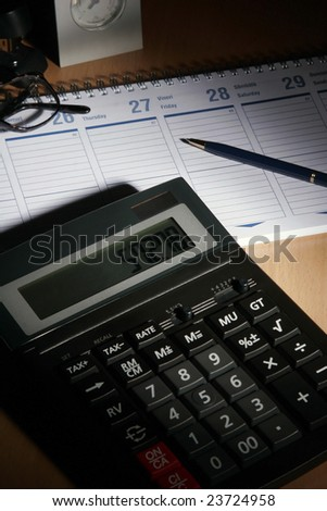 Date book on desk with calculator, glasses, pen... - stock photo