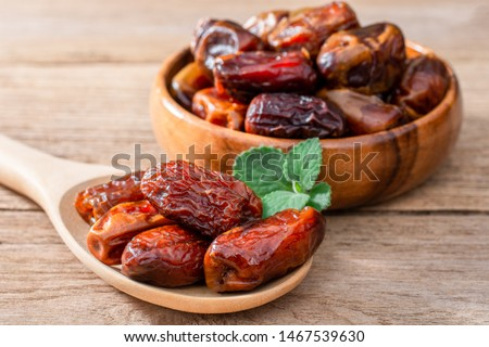 Date palm fruits in wooden bowl and spoon with mint green leaf isolated on wood table background.   #1467539630