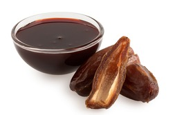 Date syrup in a glass bowl next to whole and cut dry pitted dates isolated on white.